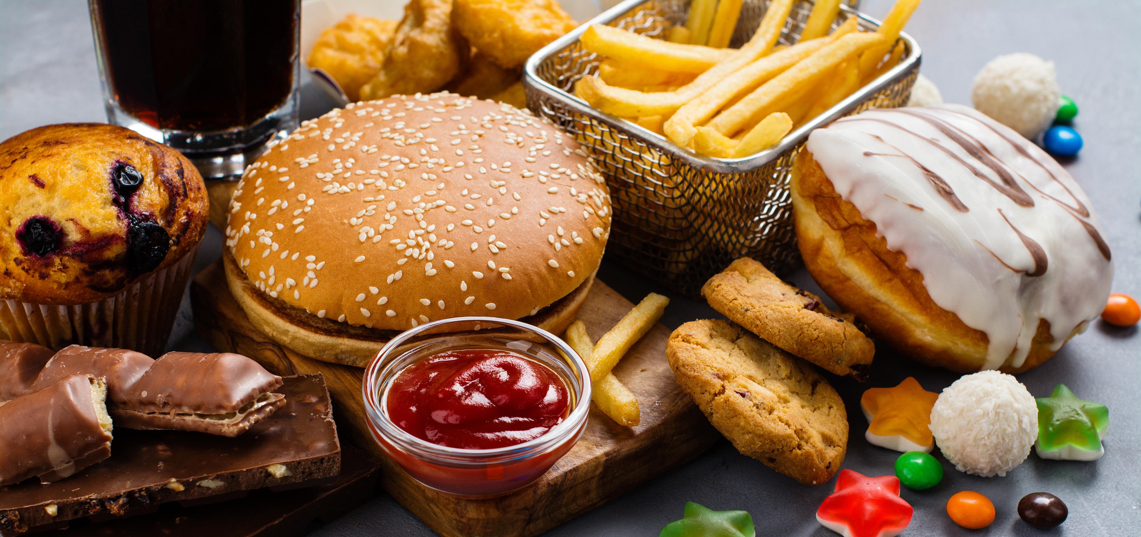 Junk foods including chocolate, hamburger, fried fast foods, iced doughnut, cola, and sugary sweets